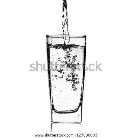 Water pour into glass on white - stock photo