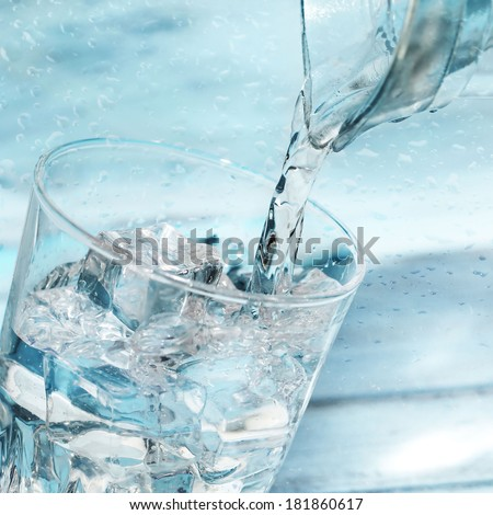 Water poured from a jug into a glass - stock photo