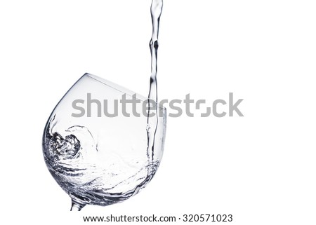 Water pouring into wine glass - stock photo