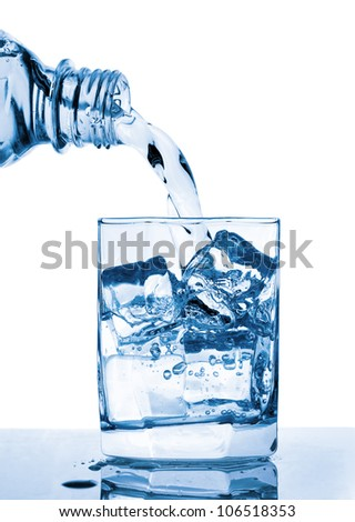 Water pouring to glass from bottle - stock photo