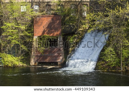 Water power sluice emerges from historic Dart's Stone Mill on the Hockanum River in Rockville, Connecticut. - stock photo