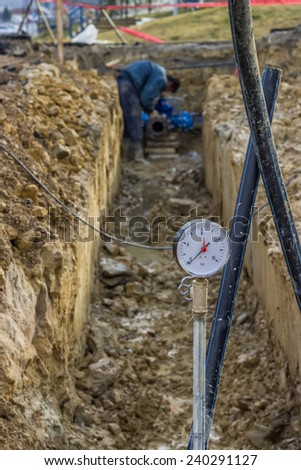 Water pressure gauge for pressure testing of water main. The red pointer show the highest pressure reached. - stock photo