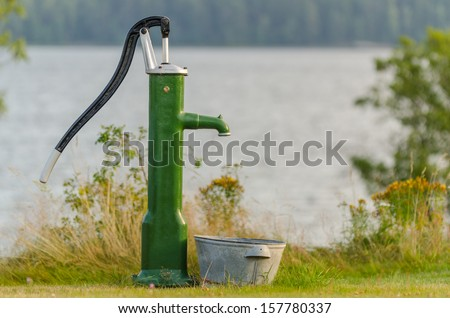 Water pump in front of a lake in summertime - stock photo