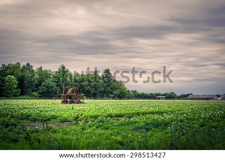 Water pump on a green field in dark cloudy weather - stock photo