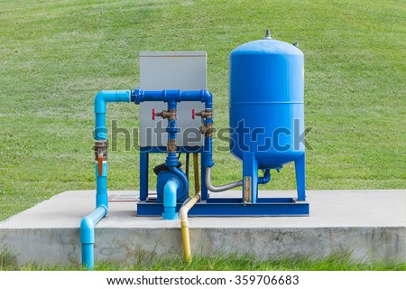 Water pump system on concrete and green grass - stock photo
