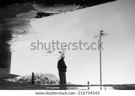 water reflection of a man standing alone - stock photo