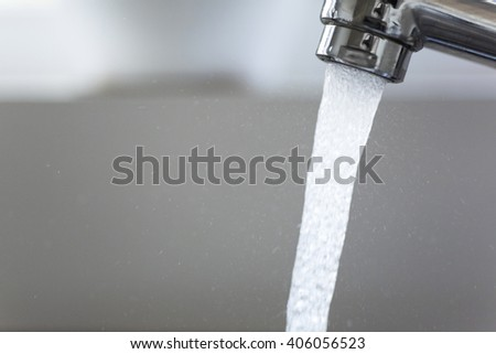 Water running from a tap into a kitchen sink - stock photo