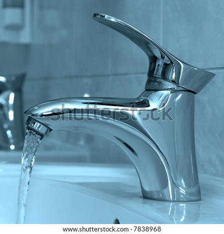 Water running from an open water faucet - stock photo