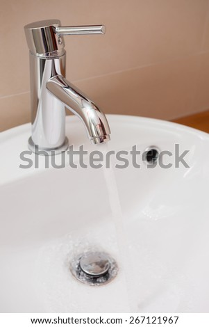 water running out from stainless steel tap to a  washbasin in bathroom - stock photo