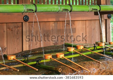 Water running out through bamboo pipe to water basin at Shimogamo jinja in Kyoto, Japan. Water ablution pavilion (Temizuya) is to purify oneself before visiting shrine in Japan - stock photo