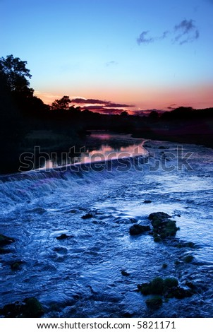 Water running over weir at sunset at Grassington, Yorkshire Dales National Park, North Yorkshire, England - stock photo