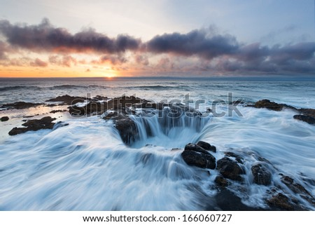 Water rushes into Thor's Well on the Pacific Ocean as the sun sets over Oregon.   - stock photo