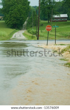 Water rushes over a roadway in rural Indiana after heavy rains - stock photo
