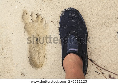 Water shoe and footprint on the sandy beach  - stock photo