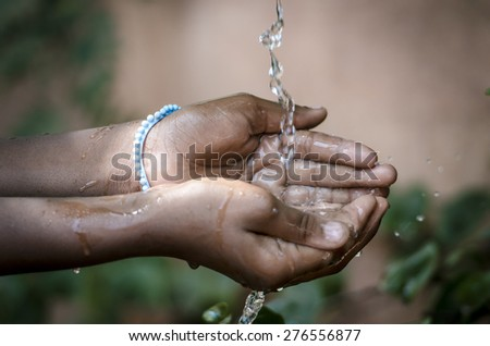 Water Spilling Into Black African Children's Hands (Drought / Water Scarcity symbol). Water scarcity is the lack of sufficient available water resources to meet the demands of water usage. - stock photo