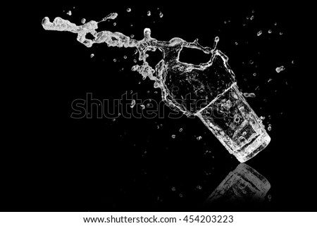 Water splash out of glass on a black background.  - stock photo