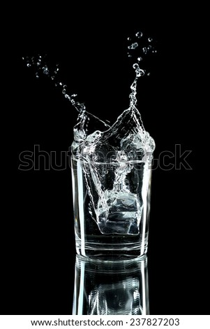 Water splash with ice in glass isolated on black - stock photo