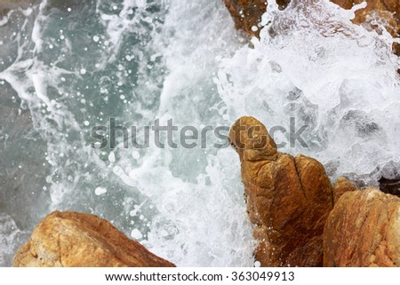 Water splashing. Crystal clear sea water beating against the rocks and cliffs. - stock photo
