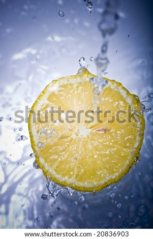 Water splashing down on a lemon with reflection - stock photo