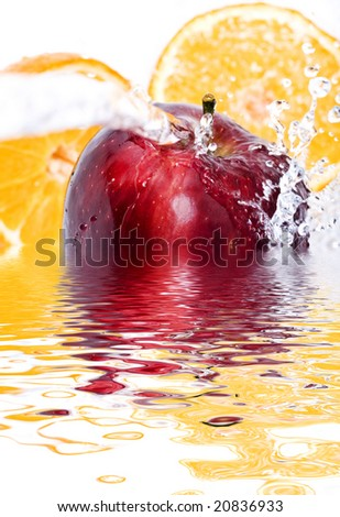 Water splashing down on an apple and oranges - stock photo