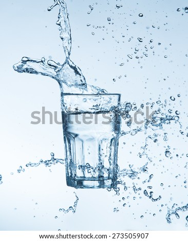 water splashing from glass isolated on white background - stock photo