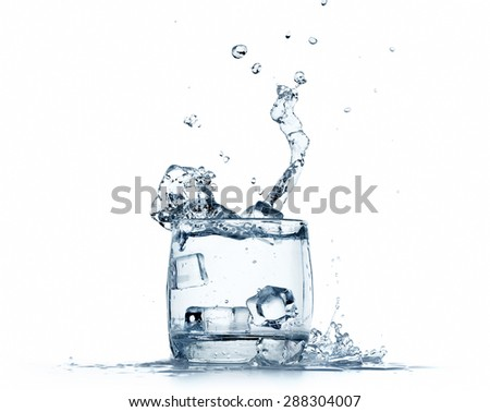 Water splashing from glass on white background - stock photo