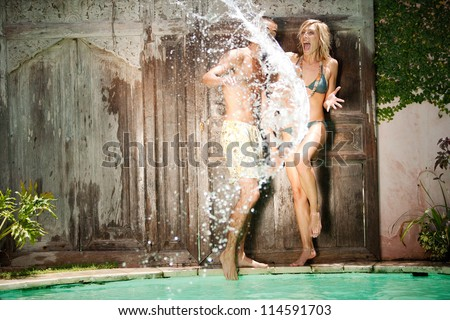Water splashing onto a young couple near a tropical swimming pool. - stock photo