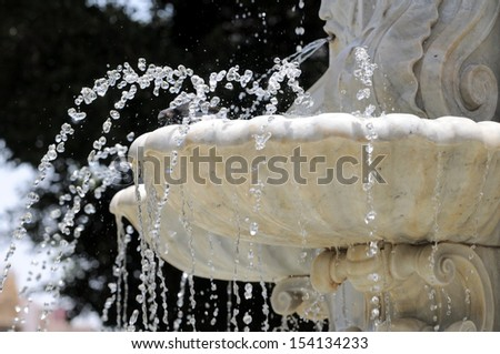 Water Splashing out of a Marble Fountain and Pigeon in Santa Cruz de Tenerife, Spain - stock photo
