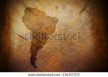 Water stain mark in the shape of the South America continent map on a vintage brown leather parchment. - stock photo