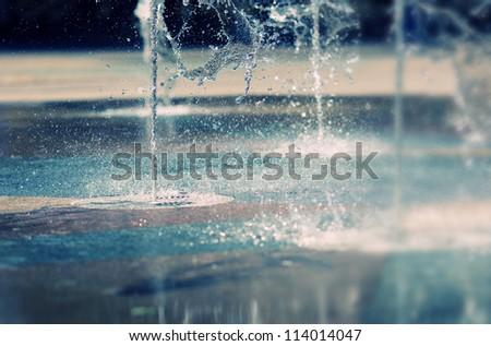 Water stream splashing on ground - stock photo