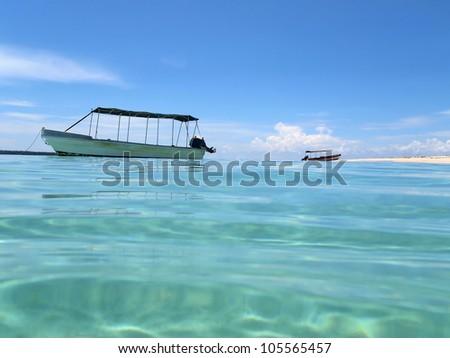 Water surface ripples with a boat anchored and sandy beach, Caribbean sea, Zapatilla island, Panama - stock photo