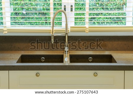 Water tap and sink in kitchen at home - stock photo