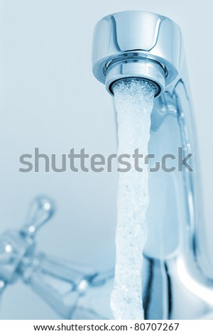 Water tap with a water stream. Blue tone image - stock photo