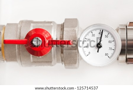 Water thermometer with red valve and metal pipes - stock photo