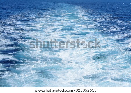 Water thrust behind departing boat - stock photo
