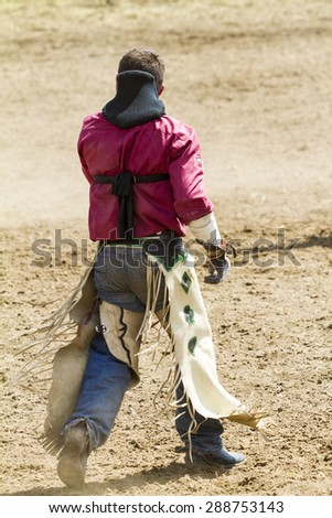 WATER VALLEY, CANADA - JUN 6 2015:Unidentified Cowboy participating in the Calf Roping at the Water Valley Rodeo.This annual event is important for the rural as well as the sport loving community. - stock photo
