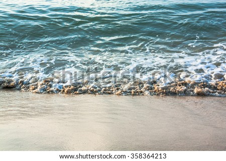 Water Wave on the sand beach. - stock photo