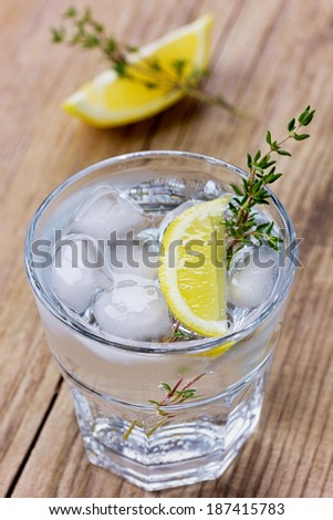 Water with lemons and ice decorated herb thyme on a rustic wooden table   - stock photo