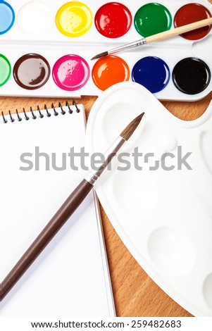 Watercolor paint, brushes and notebook on a wooden background. - stock photo
