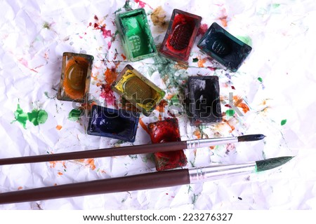 Watercolor paint cubes with brushes and spilled paint on white paper background - stock photo