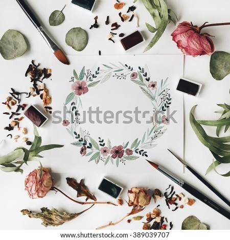 Watercolor painting, brushes, roses and green leaves at white background. Flat lay, top view. wreath frame - stock photo