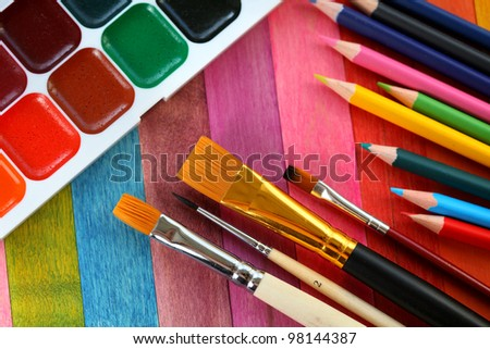 watercolor paints with brushes and colorful pencils - stock photo