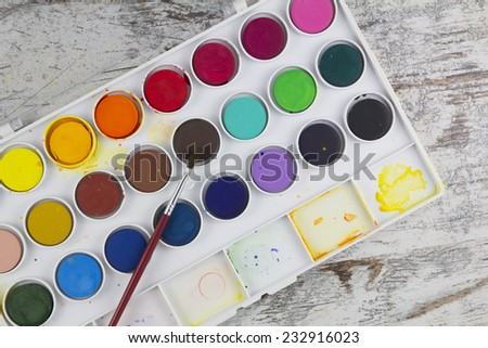 Watercolor palette with paintbrush in a wood background - stock photo