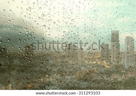 Waterdrops on a glass surface windows with cityscape background - stock photo