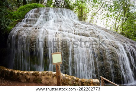 Waterfall among rocks invaded by greenery. Summer sunny, natural park. - stock photo