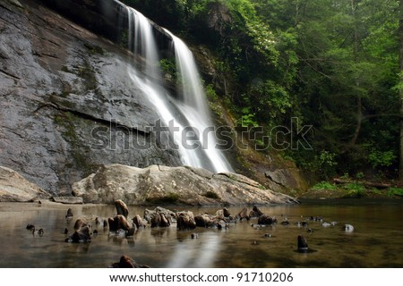 Waterfall and boulder in lush green forest - stock photo