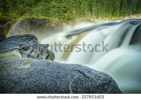 Waterfall and rainbow in Norway - stock photo
