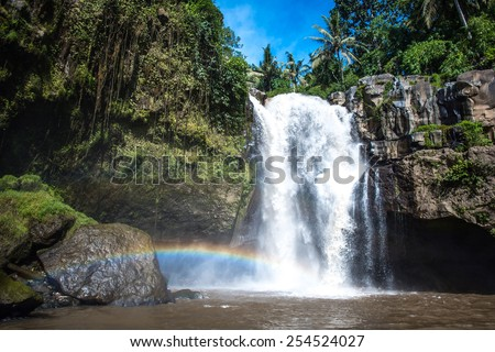 Waterfall and rainbow surrounded with green tropical forest and rocks, horizontal - stock photo