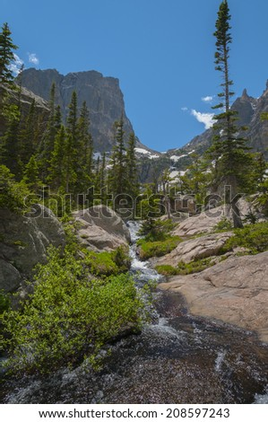 Waterfall cascade along the hiking trail to Emerald Lake view of Flattop Mountain and Hallett Peak-Colorado Rockies - stock photo