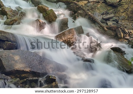 Waterfall cascading over jagged rocks. - stock photo